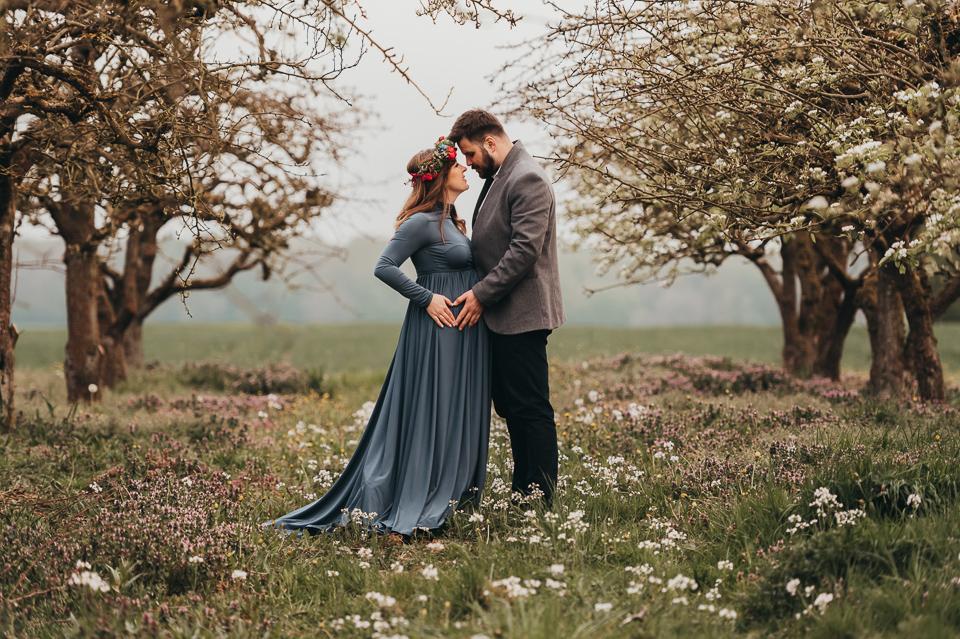 Sesja ciążowa w kwitnącym sadzie